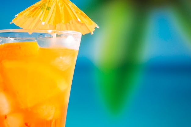 Glass of fresh orange drink decorated with bright umbrella