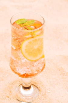 Glass of fresh orange drink with sliced citrus and mint
