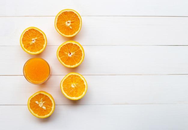 Glass of fresh orange juice with fresh fruits on white wooden background.