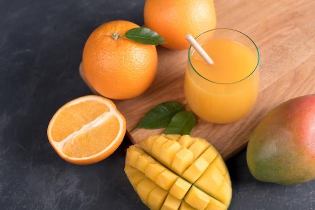 Glass of fresh orange and mango juice and slice of orange fruit on dark table