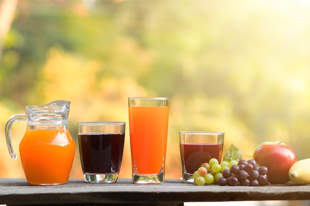 Glass of fresh organic juice with fresh fruits on wooden table over green bokeh background