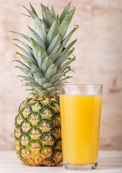 Glass of fresh pineapple juice with raw fruit on wooden background