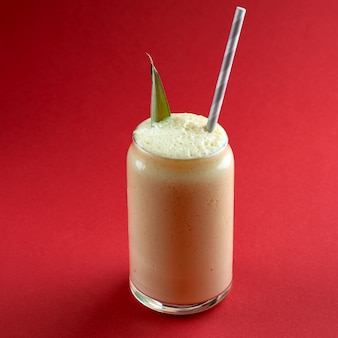 Glass of fresh pineapple smoothie decorated with a pineapple leaf, detox diet concept, on red surface