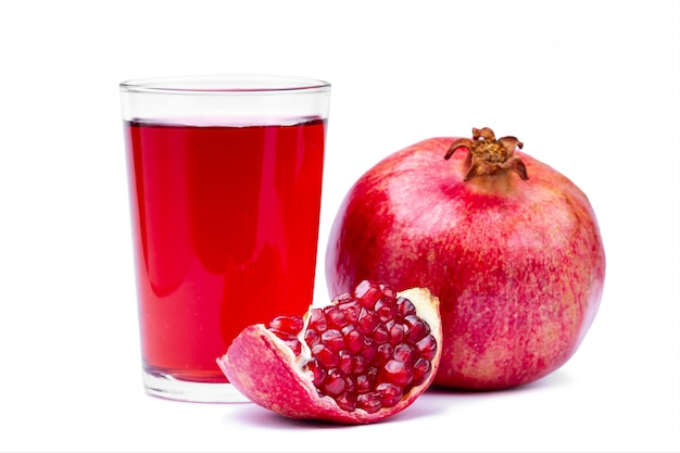 Glass of fresh pomegranate juice, ripe pomegranate and clipping path with red seeds isolated on white background