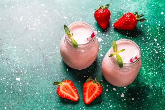 Glass of fresh strawberry milkshake, smoothie and fresh strawberries,healthy food and drink concept.