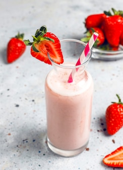 Glass of fresh strawberry milkshake, smoothie and fresh strawberries, healthy food and drink concept.