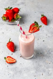 Vetro del frappé fresco della fragola, del frullato e delle fragole fresche, dell'alimento sano e concetto della bevanda.