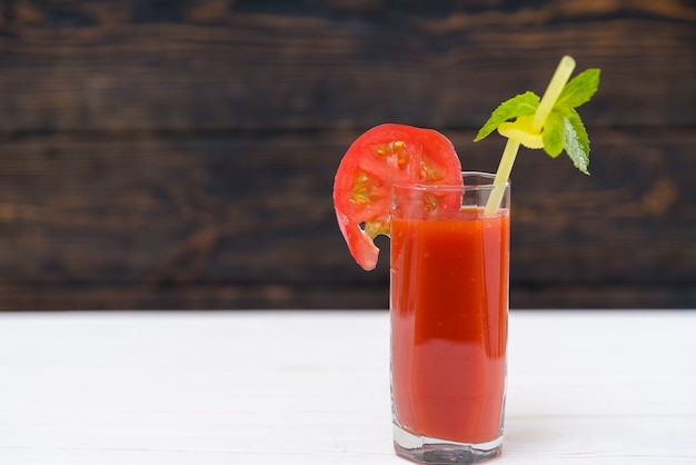 Glass of fresh vegetable juice with slice of tomato and mint leaf on plastic straw
