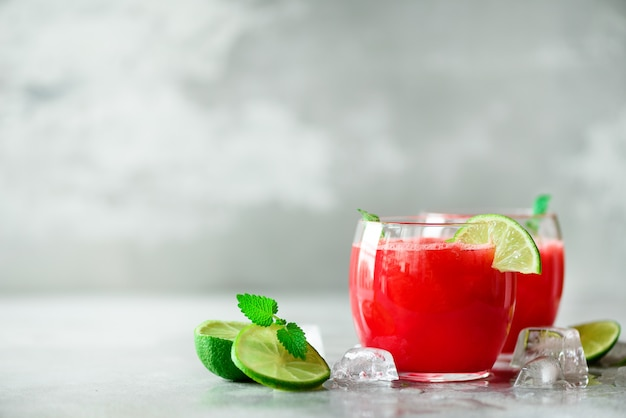 Glass of fresh watermelon juice with lime, mint, ice