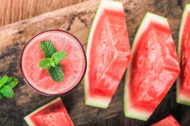 A glass of fresh watermelon juice on a wooden board background