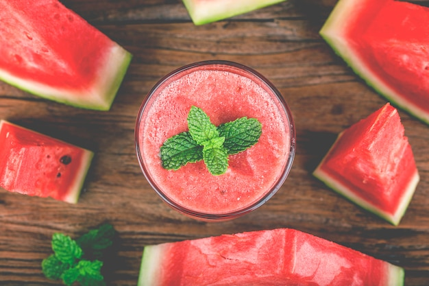 A glass of fresh watermelon juice on a wooden board