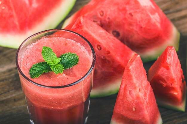 A glass of fresh watermelon juice on a wooden board