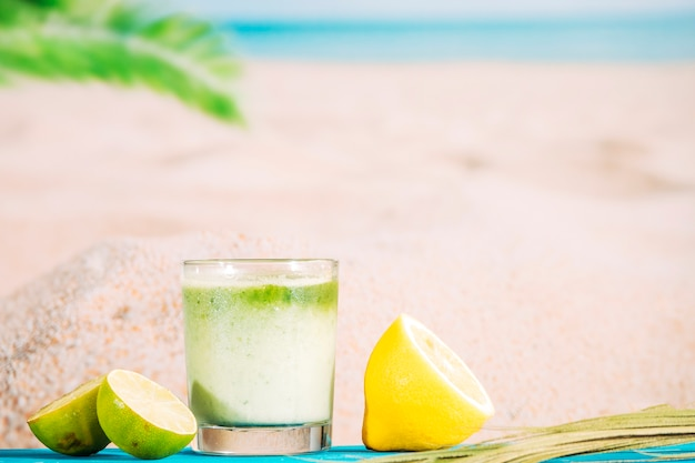 Glass of fresh whipped smoothie and sliced citrus