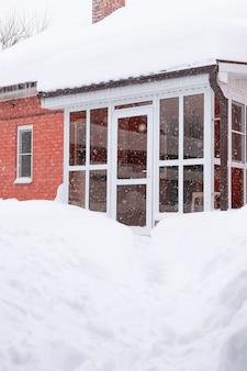 Стеклянная входная дверь дома из красного кирпича со снегом во время снежной снежной бури зимняя погода