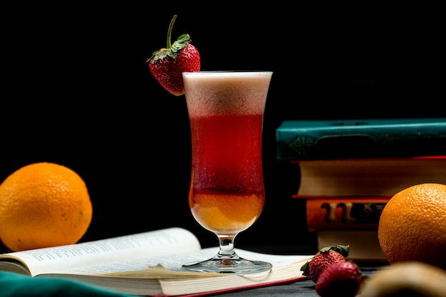 Glass of fruit cocktail with orange and strawberry