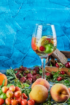 A glass of fruit juice, box of cherries, fresh strawberries and peaches on blue surface