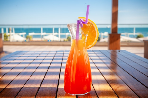 A glass of fruit juice on the ground with beach, side view.