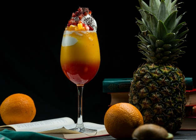 A glass of full mixed tropical fruits cocktail with rich colors standing on a book leaves