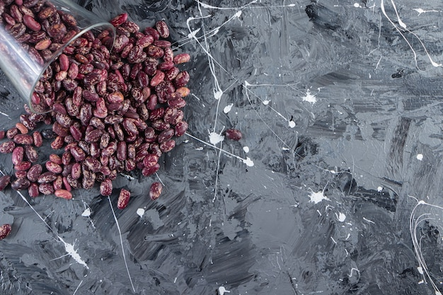 원시 콩으로 가득 찬 유리는 돌 배경에 놓여 있습니다.