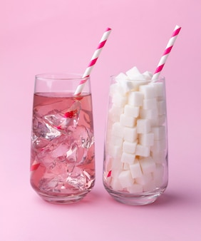 Glass full of sugar cubes and glass of soda water. unhealthy food concept.