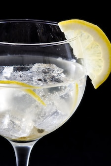Glass of gin tonic with lemon on black background close up