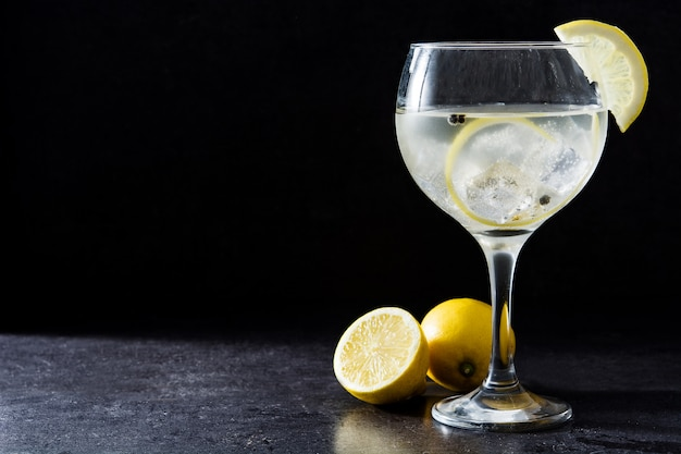 Glass of gin tonic with lemon on black background copy space