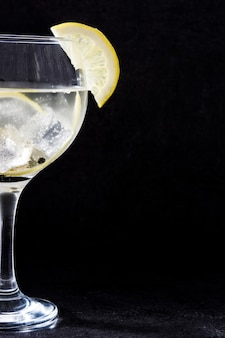 Glass of gin tonic with lemon on black background