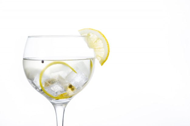 Glass of gin tonic with lemon isolated on white background