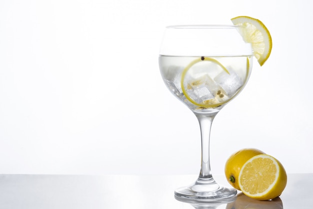 Glass of gin tonic with lemon isolated on white