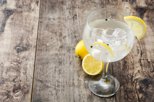 Glass of gin tonic with lemon on wooden table