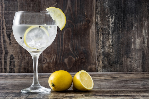 Glass of gin tonic with lemon on wooden