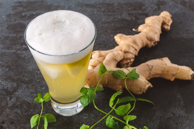 A glass of ginger beer on a black marble background with ginger and fresh mint. ginger beer is a thirst-quenching and low alcoholic drink.