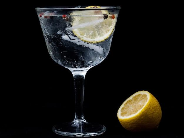 Bicchiere di gintonic con limone e ghiaccio isolato su una parete nera