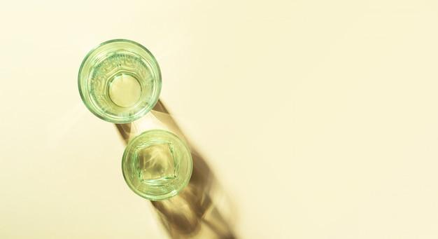 硬い光と反射で明るい背景にきれいな水でガラスガラス。歪んだガラス水