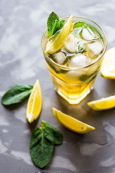 A glass glass with a cold tea with ice, mint and lemon on a gray concrete background.