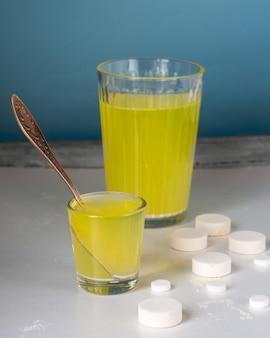 オレンジフレーバーの可溶性ビタミンを含む大小のガラスガラス