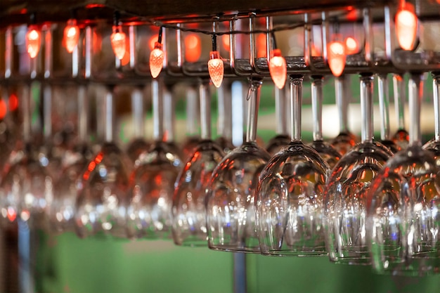 Glass glasses with red lights hang in the bar. high quality photo