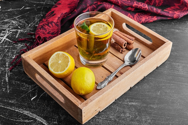 A glass of glintwine with lemons in a wooden tray.