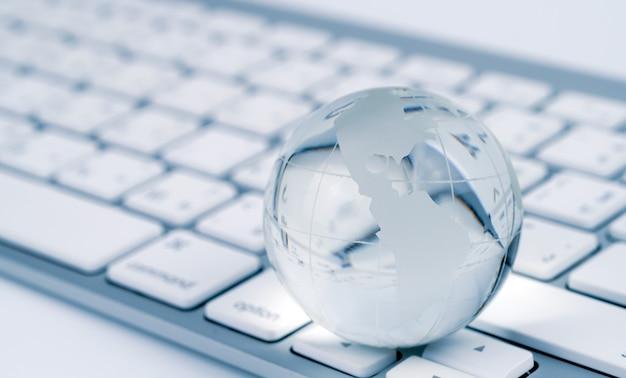 Стеклянный глобус и клавиатура мир бизнес и экономика