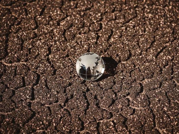 茶色の乾燥した亀裂土壌の土地の背景、上面図のガラスグローブ。亀裂床の背景にクリスタルアース。乾燥地。地球温暖化。グローバルな熱効果。