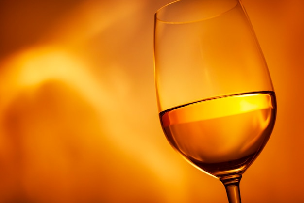 Glass of glowing golden white wine on orange wall