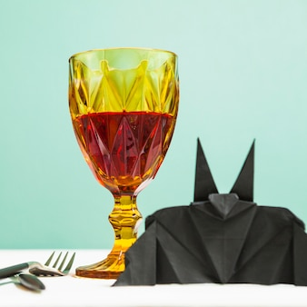 Glass goblet and bat origami standing on table