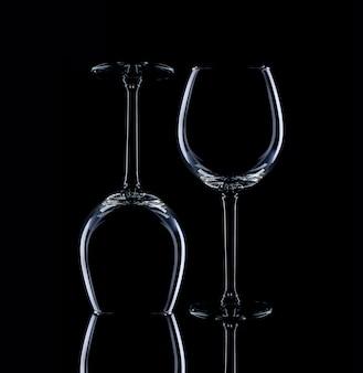 黒の背景に細い茎のガラスのゴブレット