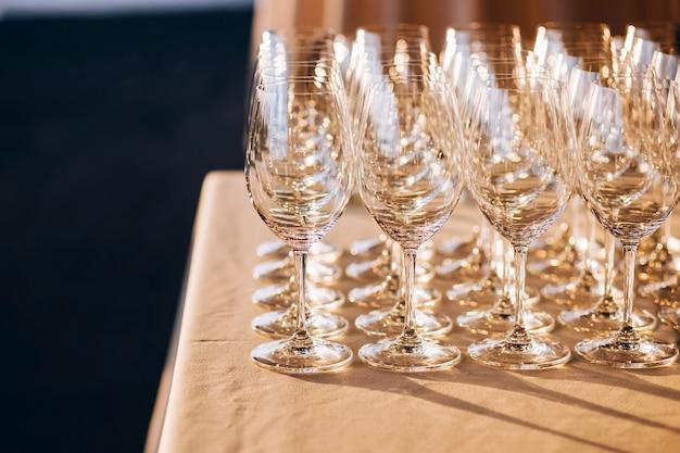 白いテーブルの上のガラスのゴブレット。空のクリスタルワイングラス。高い脚にガラスの杯。白いテーブルクロスに多くの空のグラス
