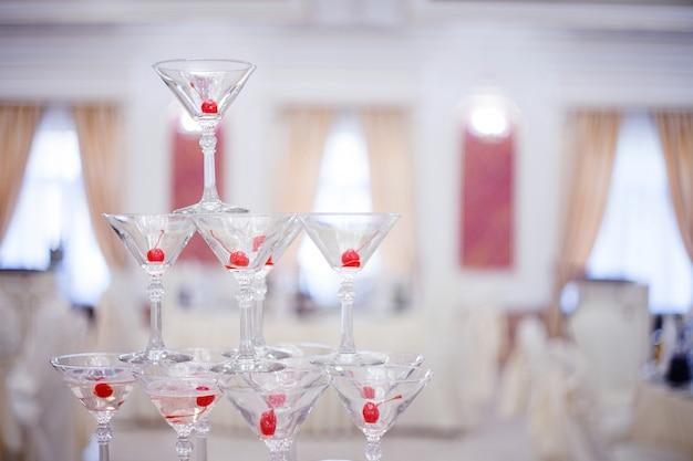 ガラスのゴブレット。シャンパンのピラミッド。丘のグラスワインとチェリー。アルコール用。お祝いドリンク。宴会を飾ります。浅い被写界深度
