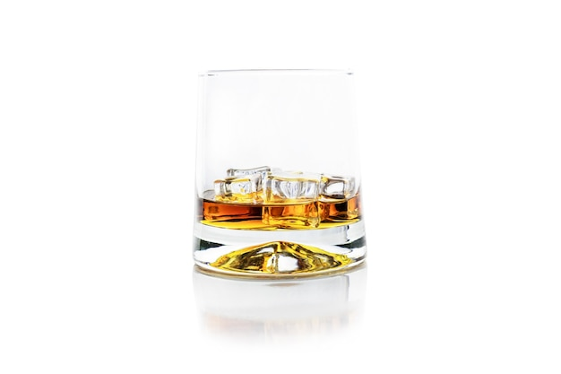 Glass of golden alcohol with ice cubes on white reflective surface, whiskey or cognac, isolated on white.