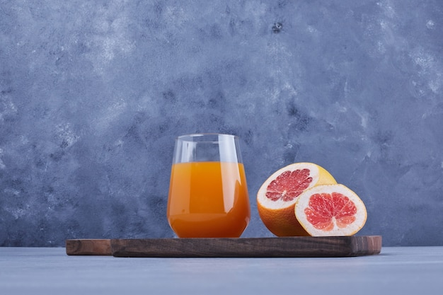 A glass of grapefruit juice with fruit slice around.
