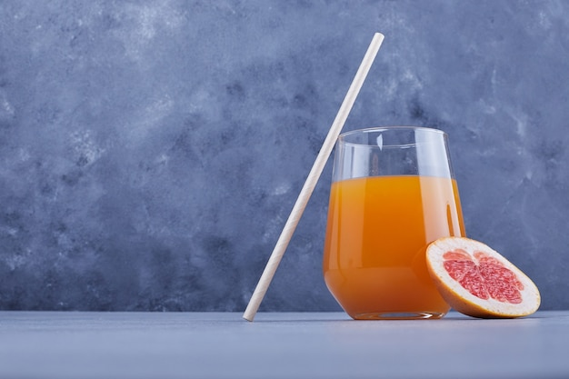 A glass of grapefruit juice with pipe.