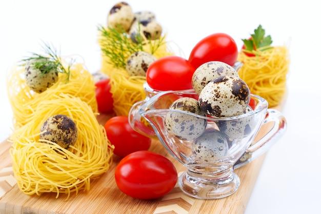 메추라기 알을 곁들인 유리 그레이비 보트. 파스타 둥지와 체리 토마토의 배경.