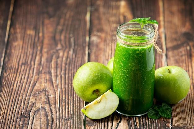 Bicchiere di frullato sano mela verde messo accanto a mele verdi fresche